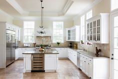 I would love to renovate my home in a similar way to this. I especially like the low hanging chandeliers. The white theme with dark color accents really allows the colors pop. I will dream of this kitchen in my future home.
