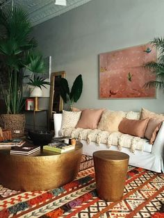 stunning boho style living room with high ornate ceilings and loads of plants | brass coffee table | white sofa with abundance of pillows and a Moroccan wedding blanket | brightly patterned vintage rug | Get inspired and make the look your own with an IKEA Färlöv sofa and a Bemz cover in Soft White Belgian Linen
