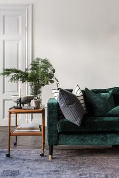 Elegant Scandinavian interior | Dark green velvet sofa | retro style bar cart with seasonal greenery on it | striped cushion covers | simple holiday decor | IKEA Karlstad sofa with a Bemz cover in Viridian Zaragoza velvet