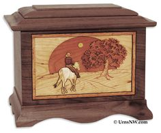 Walnut wood urn with oak, cherry, and maple inlays which together create a lifelike 3-Dimensional wood art scene of a rider and horse down their final journey home. Made in the USA.