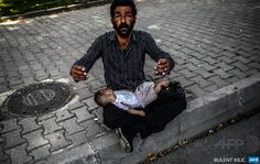 Syrian refugee gestures as he begs with a baby on his lap in Istanbul on June 19, 2014. Syria's army had recaptured the strategic town of Kasab and the only border crossing with Turkey in Latakia province, after it fell to rebels almost three months ago. Nearly half of Syria's population has fled their homes since the uprising against President Bashar al-Assad's rule erupted in March 2011. AFP PHOTO/BULENT KILIC