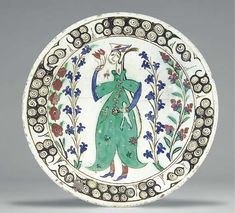 AN IZNIK POTTERY DISH OTTOMAN TURKEY, CIRCA 1640 With sloping rim on short foot, the white interior painted in green, red and blue, with large standing woman in green tunic holding a pair of tulips, flanked by red and blue floral sprays, the rim with cloud and scroll motif, the exterior with simple alternating green and blue motifs, 11¼in. (29cm.) diam.