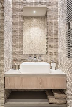 In the husband's ensuite bathroom, the walls are clad in custom-cut natural limestone tiles that bring a textured yet sophisticated look. The custom vanity features a honed quartzite top, dyed timber drawer front and open stone shelf below.