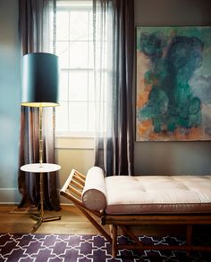 Moody Living Room - A daybed beside a gold floor lamp with a black lampshade.  Geometric rug.