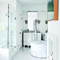 floating frame art, white fireplace, fireplace in bathroom, white marble tiled floors, seamless frameless glass corner shower, white vanity with mirrored doors, white x front mirrored vanity, round white and gray ottoman, marble tiled shower surround, beveled vanity mirror, antiqued silver wall sconce, glamorous bathroom, bathroom ottoman, master bath fireplaces, corner shower, vanity with mirrored doors, washstand with mirrored doors