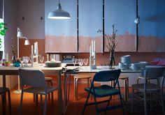 Jedálenský stôl cez deň. Nástenné úložné priestory IKEA sú skryté za stiahnutými roletami.