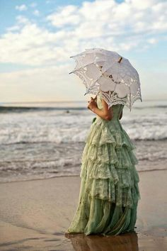 White eyelet umbrella and green gown by the beach