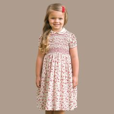 Girls ivory dress with a pretty, red, floral print by Sarah Louise, featuring wonderful hand smocking and hand embroidery on the bodice. Made in a smooth, lightweight cotton blend, it has a lovely Peter Pan collar, piped in red with embroidered lattice detailing, matching the puffed sleeves. Fully lined, it has a button fastener at the back, with a neat, buttoned, back waistband.