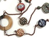 Handmade wrap necklace which combines bottle cap beads with hand formed ceramic clay beads and copper.