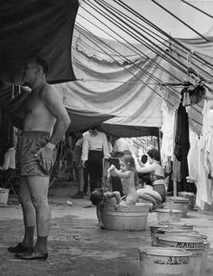 Circus performers bathe in tin buckets beneath the tent . C. 1937, Chicago. Kenneth Heilbron