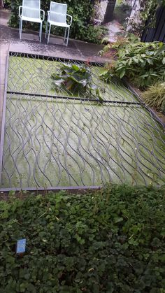 Strakke rechthoekige vijver afgedekt met sierlijke metale mat, Appeltern