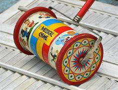 """.These old tin toys with the colorful lithographed Nursery Rhyme illustrations are so charming! The colors are so great. Tin drum with wooden wheels and handle. About 23"""". Made by Fisher Price in 1951"""