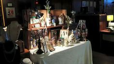 4 foot table indoors. Altered art bottles & jars with bag charms