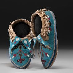 Assiniboine Beaded Hide Moccasins thread and sinew-sewn using small glass beads in faceted colors of red white-heart, pony trader blue, white, medium blue, amber, black, and brass to create a floral pattern on vamps; fringed cotton cuffs; fully beaded split tongues, length 10.25 in. fourth quarter 19th century Condition: Moccasins sparkle; insignificant bead loss; exhibits signs of use. Price Realized Including Buyer's Premium $1,800 04/10/2015