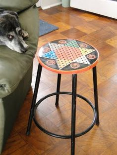 the tin lid of an old chinese checkers box screwed onto a stool base