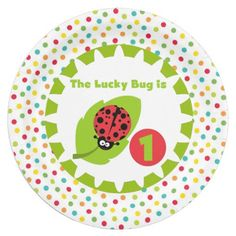 Lucky Ladybug 1st birthday party paper plates features a big green leaf with a black and red spotted ladybug, text that reads The Lucky Bug is 1, and lots of polka dots of red, green, blue, orange, and yellow on white! The 1st birthday celebration will be spectacular with these colorful ladybug theme birthday party paper plates!
