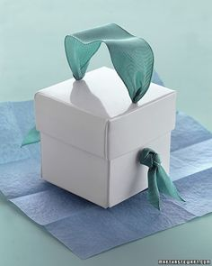 Ribbon Handle A blue ribbon threaded through the lid and sides and secured with knots creates a handle for this box.