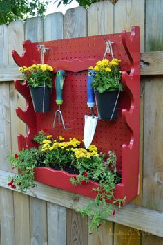 How to repurpose a gun rack. Red hanging plant display / garden tool storage. Functional garden / yard decor #DIY #upcycle #gardendecor www.astralriles.com #ReDesign #ReInvent #ReLive