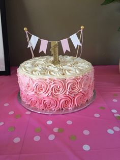 Pink and gold themed girl's first birthday party. Raspberry cake filled and frosted with vanilla buttercream. Ombré pink rosettes