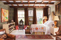 The master bedroom holds treasure from China, India, Syria, and Turkey; the leather armchair is from Newel.
