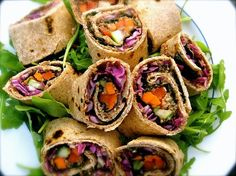 An original way to prepare a vegetable sushi-roll: Nori is placed alongside whole wheat tortilla wraps and filled with a black soybean paste, red and yellow peppers, carrots, cucumbers, and red cabbage. Enjoy!