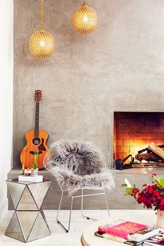 Living space with concrete walls, a fireplace, and a modern metal chair