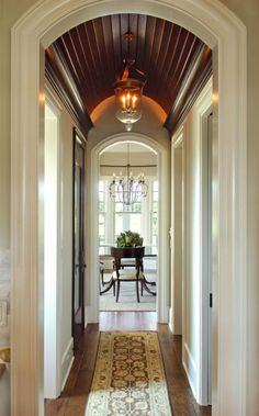 Hallway -- would like to make my arched  doorways extravagant by using larger trim and that ceiling linking the two arches.