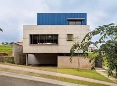 Casa mistura concreto, tijolos aparentes e telhas metálicas em busca de conforto térmico