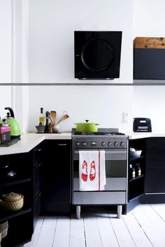 White washed kitchen with black cupboards and appliances.