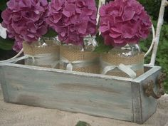 Simple burlap and ribbon wrapped mason jars with hydrangeas.