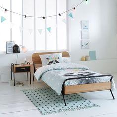 Une chambre d'enfant style scandinave. L'esprit scandinave se glisse même chez les plus petits : ce lit d'inspiration vintage accompagné de la table de chevet se marie savamment aux détails poétiques subtilement bleutés.