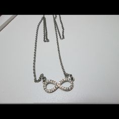 Silver infinity necklace About 9 inches in length. Bejeweled infinity jewel connected to the chain. No rust and still very shiny. Jewelry Necklaces