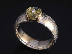 Sapphire and mokume engagement ring; bi-color sapphire and bi-gold and silver etched mokume. Contemporary and cool!