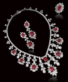 SPECTACULAR RUBY AND DIAMOND PARURE, ASPREY. Comprising: a necklace composed of a graduated line of brilliant-cut diamonds supporting at the front a fringe of oval and cushion-shaped rubies set within oval, pear-shaped and brilliant-cut diamond surrounds, accompanied by a pair of pendent earrings and a ring en suite, mounted in platinum and yellow gold, signed Asprey, French assay and maker's marks.
