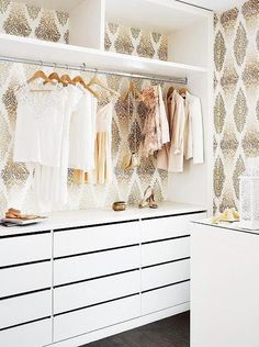 Girly walk in closet with white drawers, a shelf for shoes, hangers and wall paper with gold diamond filigree pattern