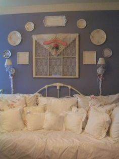 love the daybed filled with pillows and plates on the wall