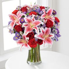 The FTD® Stunning Beauty™ Bouquet :  This elegant vased arrangement will catch their eye with its array of red roses, pink lilies, purple irises, purple aster and more. Call Americas Florist Today 212-921-8150 or visit our website at: www.americasfloristnyc.com  Same day delivery within hours.