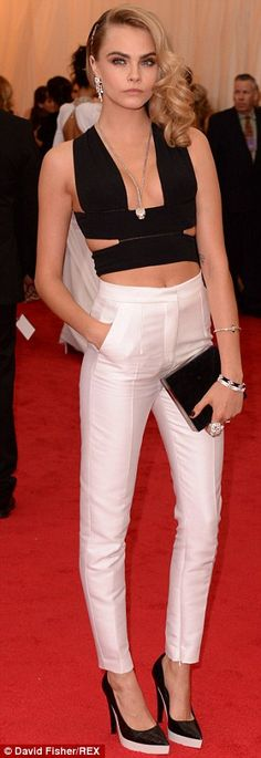 Blonde beauty Cara Delevingne: The 21-year-old showed off her toned midriff in a plunging strappy black top. Met Gala 2014