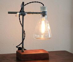 Industrial lamp made with a 500ml Erlenmeyer flask, cedar wood base and reclaimed laboratory equipment. Comes with a nostalgic Edison-style 25W candelabra bulb, cloth-covered wire and heavy duty cord switch. The cedar wood has been sanded smooth and finished with an all-natural, non-toxic finish from Heritage Natural Finishes. An uncommon accent for any desk, dresser or night stand. 12 inches tall.  **For buyers outside of North America, Japan and Brazil: This lamp (including the bulb) is…