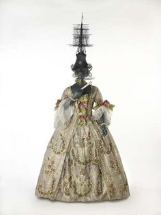 This gown is made of a very thin, plain weave silk or taffeta with very fine stripes of red, blue and white, which, seen from afar, give the impression of mauve. A white leaf pattern is woven into the fabric and as well as floral sprays in various colours. Ugly hat! Production Date: 1762-1767