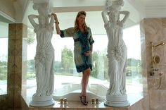 Jacqueline Siegel, wife of David Siegel, poses with statues in their home.