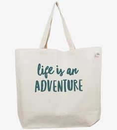 """Featuring a hand-lettered ode to the outdoors, this tote bag reads, """"Life is an adventure."""" The text is hand-drawn in thick brushstrokes and screenprinted onto the heavy canvas with green ink. The cotton canvas tote bag is roomy enough to carry all of your gear or groceries, and the sturdy material can handle heavy loads."""
