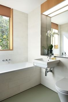 White finishes in the bathroom reflect the light, lending it bright, breezy appeal.