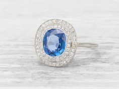 Antique Edwardian engagement ring set with a cushion-cut sapphire, with an old mine-cut diamond twin surround. Set in platinum.Circa 1915 This lively sapphire is a bright blue shade and shows beautifully with the contrast of delicate diamonds and platinum. The low setting makes is perfect for always wear. Diamond and gold mining has caused devastation in areas such as Africa, wreaking havoc on delicate ecosystems and communities. Choosing to go vintage, you are eliminating the need for more…