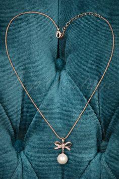 Deze 50s Phoebe Bow and Pearl Necklaceis een vintage stijl ketting met een lieflijke uitstraling! Perfect voor ale gelegenheden! Deze korte ketting in uitgevoerd in rosé goudkleurig metaal met een prachtige strikhanger, bezet met strass steentjes en afgewerkt met een classy rosé kleurige 'faux' parel. In love!   Strass steentjes Rosé goudkleurig metaal Verstelbare karabijnsluiting