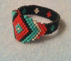 My first beaded ring and it turned out quite nice, but too big for me! I measured it at a size 13. I used fireline to thread it, so its quite