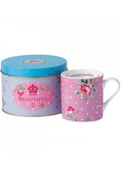 """Please yourself or a friend with this charming rose and polka dot teatime set. Inspired by one of the world's most popular china patterns, the fine bone china mug carries a special message inside the rim: """"...a beautiful friendship..."""" Scattered with pink roses and golden polka dots and topped with a powder blue lid, the pretty tin provides a perfect place for the mug, or for tea, coffee, cookies, biscuits and more. A lovely set from Royal Albert, the esteemed pottery founded in 1904 and…"""