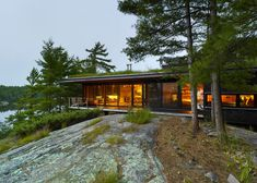 Ian MacDonald Architect has completed an island cottage in Ontario that cantilevers over a rocky hillside and is designed to be mostly hidden from view