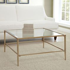 $160, birchlane.com For dens with an L-shaped couch, this metal-and-glass square table allows all guests to comfortably access a central surface. A second shelf on the bottom is a chic place to display coffee table books and other ornamental items without cluttering the top.