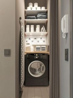 Tiny laundry room features a narrow hall lined with a black and white ironing board leading to a stacked shelves over a black front load washer.
